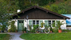 Typical German village house together with old bicycle.Typical German village house together with old bicycle. Country house with a lot of vegetation next to the Neuschwanstein castle.