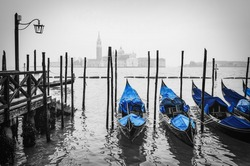 Typical gondolas stationed in old wooden dock with San Giorgio Maggiore cathedral in the distance. Venice, Italy