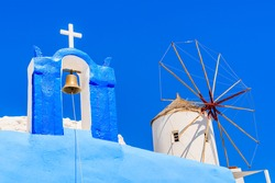 Typical Greek church tower and windmill with blue sky in background in Oia village, Santorini island, Greece
