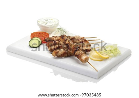 typical greek plate, souvlaki, served with tzatziki and vegetables on a marmor