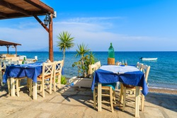 Typical Greek tavern in small fishing village on coast of Samos island, Greece