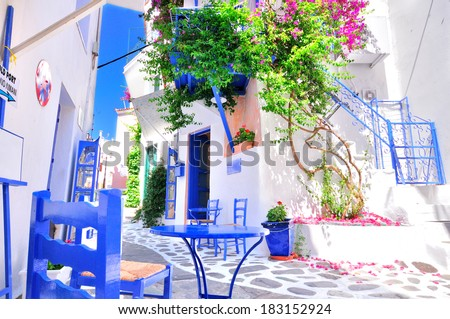 Typical greek traditional village in summer with white walls, blue furniture and colorful bougainvilla, Skiathos Island, Greece, Europe