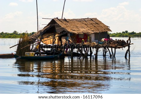 Typical House on the Tonle sap lake, with a small houseboat. Cambodia.