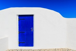 Typical house with white walls and blue door in Oia, Santorini Greece