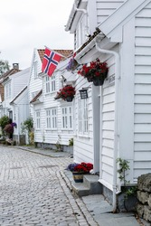Typical houses with white cladding and norwegian flag in the old town of Stavanger, Norway