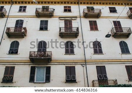 Typical italian wall with balconies and windows, brown wooden shutters. #614836316