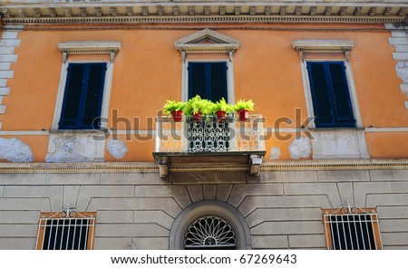 Typical Italian Windows With Closed Wooden Shutters, Decorated With Fresh Flowers