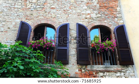 Typical Italian Windows With Open Wooden Shutters, Decorated With Fresh Flowers