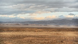 Typical landscape at Israel Jordan border as seen from car driving on Highway 90. Flat dry desert with small mountains at Jordanian side, sun shines through evening clouds
