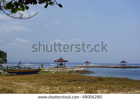 Typical little boat from Bali on the beach with three little temple on the Indian ocean in Bali
