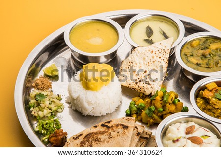 typical maharashtrian food served in a steal plate, marathi food includes kadhi and shrikhand, plain dal, spinach curry, aalu mutter, plain rice, papad, bhakri or bhakar or roti and variety of salad #364310624