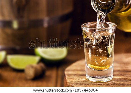 typical mexican drink bottle filling a glass of mezcal (or mescal), a rare mexican distilled beverage that contains an aphrodisiac larva or worm inside Stock foto ©