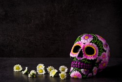 Typical Mexican skull painted and flowers on black background.Copy space. Dia de los muertos.