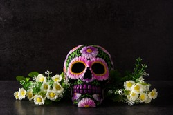 Typical Mexican skull with flowers painted on black background. Dia de los muertos.