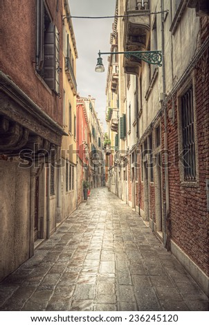typical narrow alley in street of Venice (Venezia) at a rainy day, vintage style, Italy, Europe