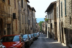 Typical narrow cobbled street with old stone houses full of cars parks only on one side in small italian ancient town Gubbio in Umbria. Urban transport challenge. Popular travel destination - image