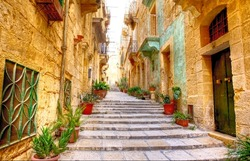 typical narrow street with stairs in the city Valetta on the island of Malta