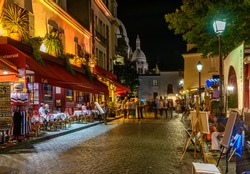 Typical night view of cozy street with tables of cafe and easels of street painters in quarter Montmartre in Paris, France. Architecture and landmarks of Paris. Postcard of Paris