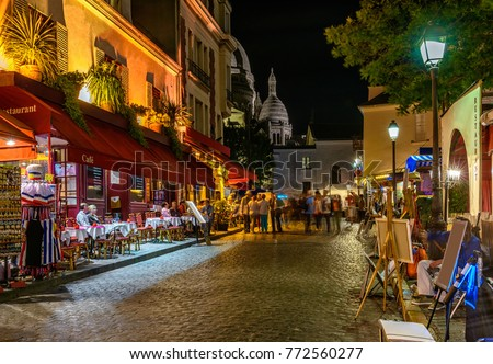 Typical night view of cozy street with tables of cafe and easels of street painters in quarter Montmartre in Paris, France. Architecture and landmarks of Paris. Postcard of Paris #772560277