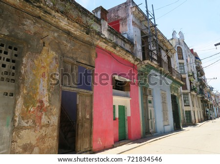 typical non central street in Havana, Cuba, with withering collapsing decaying architecture, houses falling apart, residents endangered living in such conditions, poverty and ruins #721834546