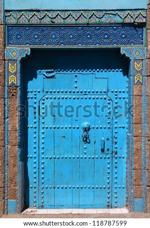 Typical, old, blue intricately carved, studded, Moroccan riad door and door-frame, Azemmour, El Jadida, Morocco.