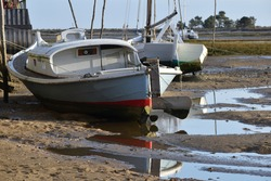 Typical old boat stranded on Cap-Ferret beach, reflections in a puddle