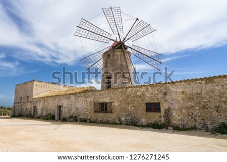 Typical old windmill now housing a salt museum (Museo del Sale) at Trapani salt flats, Sicily, Italy