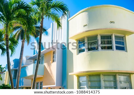 Typical pastel-colorfed 1930s Art Deco architecture with palm trees in Miami, Florida #1088414375