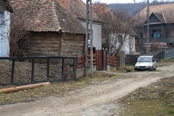 Typical poor village street view in Romania. Dirt road, ruined houses.