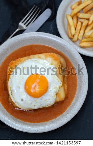 typical portuguese dish francesinha in dish and fried potato on plate on black ceramic background