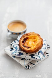 typical portuguese egg tart pastel de nata with cup of coffee on ceramic background
