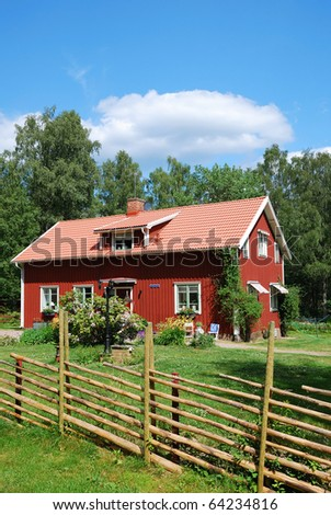 Typical red cottage is in the green yard overgrown with grass and flowers. In the background there are summer forest and the blue sky. The estate is enclosed with traditional wood fence.