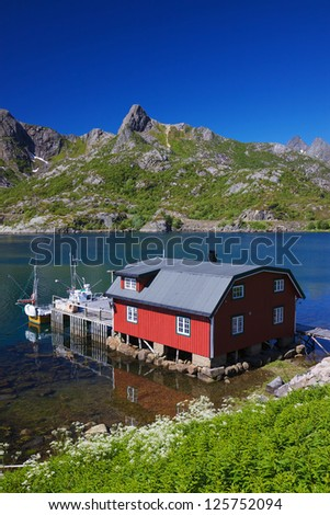 Typical red modern fishing hut in fjord on Lofoten islands in Norway