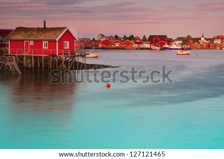 Typical red rorbu fishing hut in town of Reine on Lofoten islands in Norway lit by midnight sun