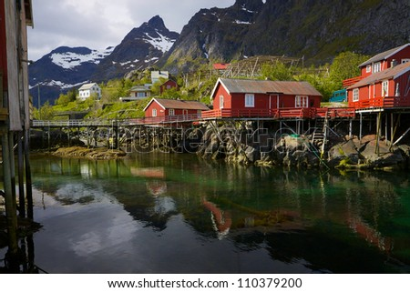 Typical red rorbu fishing huts on Lofoten islands in Norway reflecting in fjord