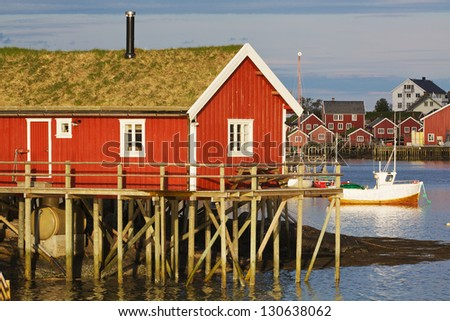 Typical red rorbu hut with turf roof in town of Reine on Lofoten islands in Norway