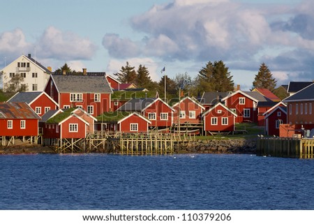 Typical red rorbu huts with sod roof in town of Reine on Lofoten islands in Norway