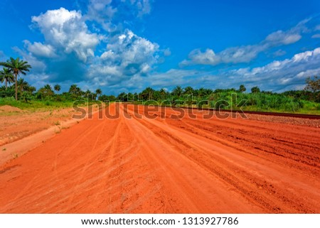 Typical red soils unpaved rough countryside road along railway track in Guinea, West Africa. #1313927786