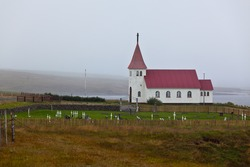 Typical Rural Icelandic church with local cemetery at overcast day