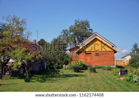 Typical Russian country house cottage with plot, vegetable garden, fruit trees and a green meadow against a blue sky