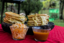 typical Salvadoran dish, cheese pupusas with cabbage and tomato sauce. rice and corn pupusas stuffed with cheese, beans or other ingredients