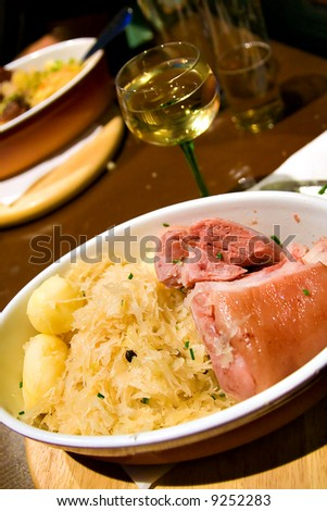 Typical Sauerkraut dish, with Wine glass (shallow DOF, focus on meat)