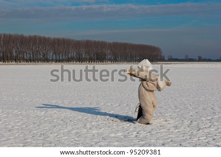 Typical scarecrow on a snowy field in the Netherlands. The snow is just fallen and still unspoiled. It is very cold.