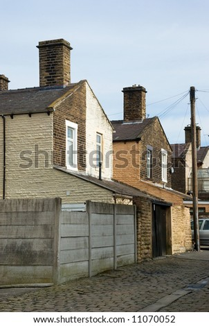 Typical scene of a cobbled street behind a row of terraced houses in a Lancashire mill town