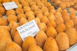 Typical Sicilian dish arancini in the window of a local fast food. on  white paper in Italian says
