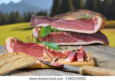 Typical South Tyrolean bacon snack with local rye bread lying on a rustic table in front alpine pastures and mountains of the alps #1380250082