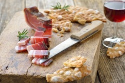Typical South Tyrolean snack with country bacon and local crunchy flat bread, served with local red wine