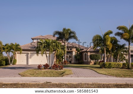 Typical Southwest Florida concrete block and stucco home in the countryside with palm trees, tropical plants and flowers, grass lawn and pine trees. Florida. South Florida single family house #585881543