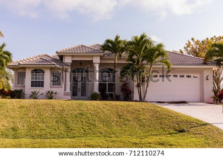 Typical Southwest Florida concrete block and stucco home in the countryside with palm trees, tropical plants and flowers, grass lawn and pine trees. Florida. South Florida single family house #712110274