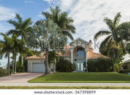 Typical Southwest Florida home in the countryside with palm trees, tropical plants and flowers, grass and pine trees. Inlaid pavement at the entrance. Florida #367398899